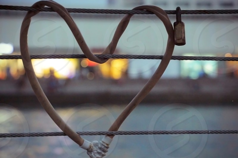 Heart-shaped padlock locked metal cables during twilight time. photo