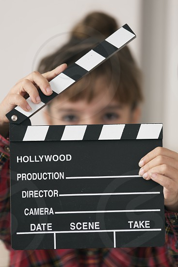 10-year-old girl with a clapboard of a hundred in her hands. Vertical shot photo