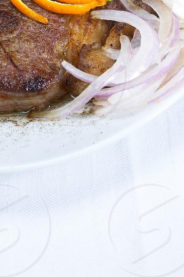 fresh juicy beef ribeye steak grilled with orange and lemon peel on top and vegetables beside photo