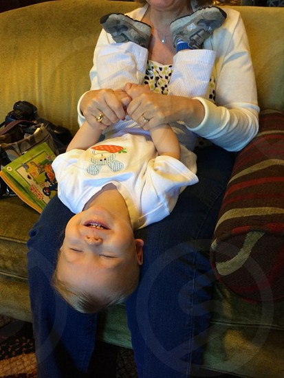 woman tickling baby smiling upside down on lap photo