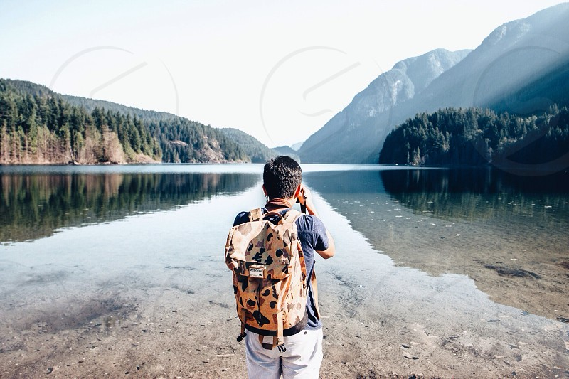 man photographing a lake photo