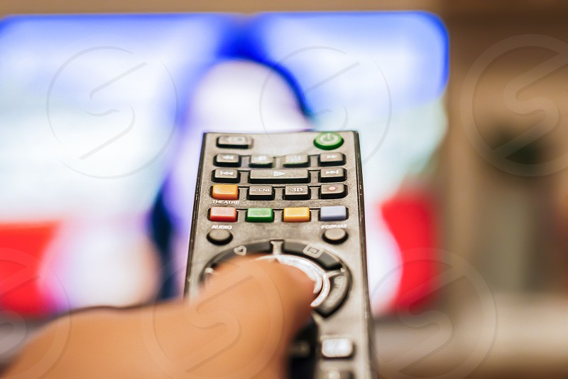 A hand pressing a remote control button to change channels in front of a blurry television screen photo