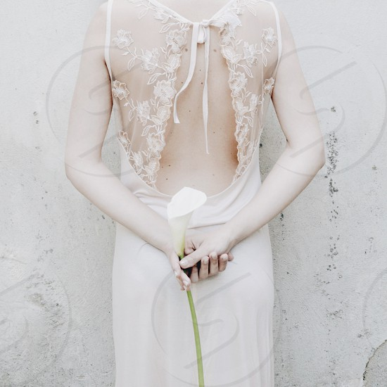 woman in white silk lace backless gown holding a lily behind her back photo