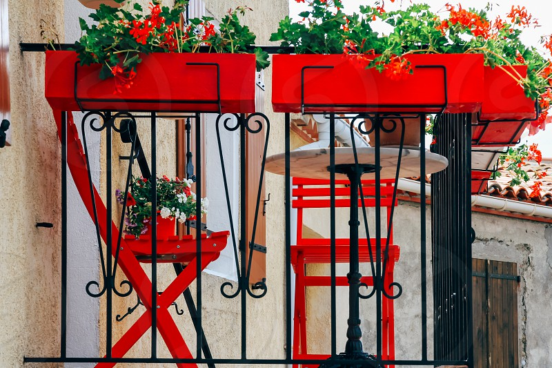 Bright red outdoor chairs window boxes geraniums small balcony French village photo
