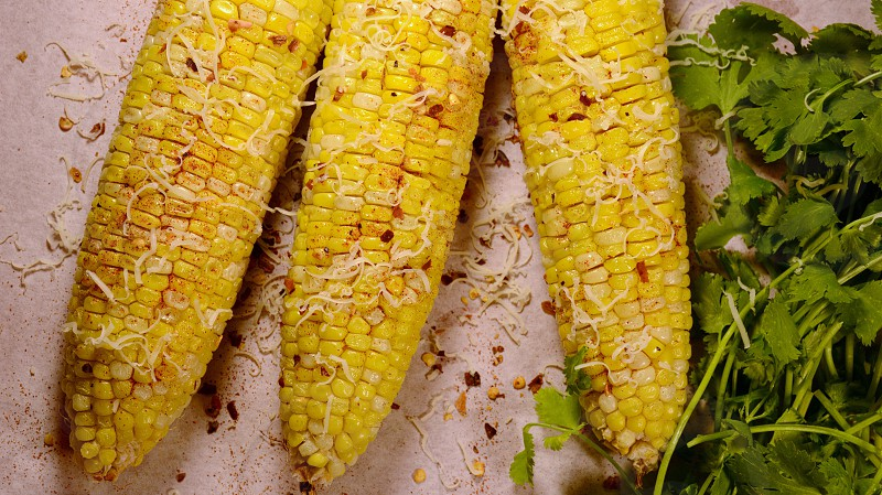 Mexican grilled corn on the cob cilantro paprika pepper flakes queso cheese. photo