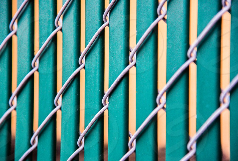 photo of grey metal frame fence n brown railings with green background photo