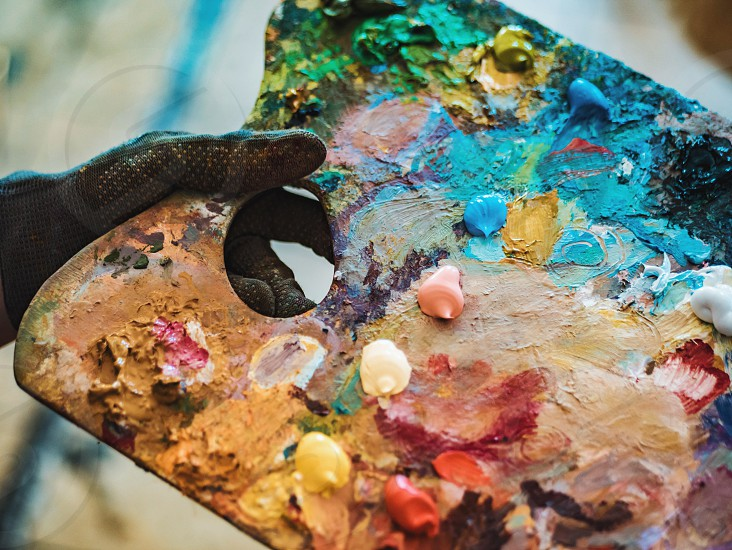 Wooden art palette with oil paints. Mixing colors together. Artistic instrument with many colors. Working tool with squeezed out tubes of paint. photo