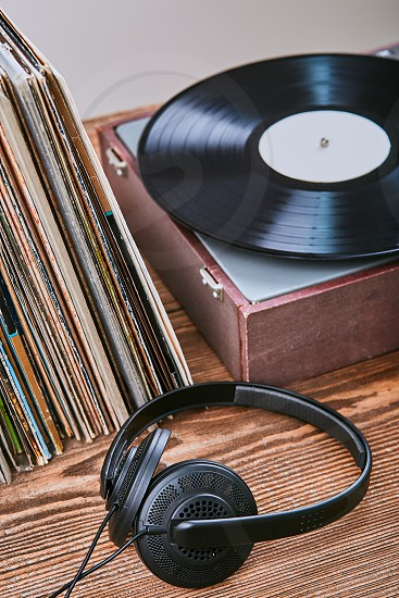 Stack of black vinyl records turntable vinyl player and headphones. Classic stereo set. Candid people real moments authentic situations photo
