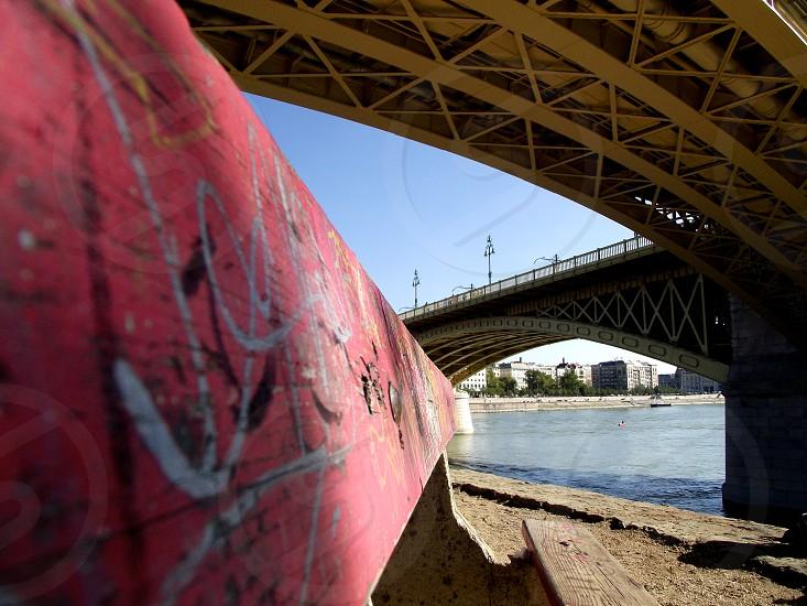 graffiti on the dike under brown concrete bridge photo