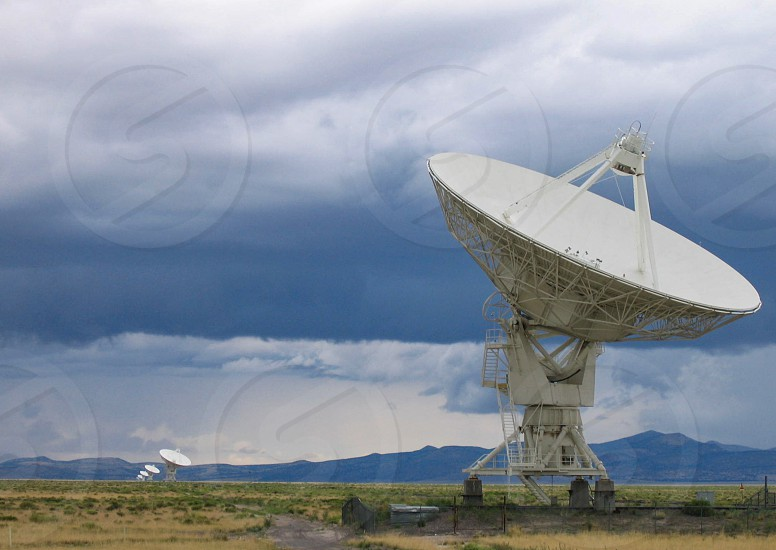 Radio telescope dishes of the Karl G. Jansky Very Large Array astronomy research facility are spread widely in this view of the Plains of Agustin in west central New Mexico under a stormy summer sky photo