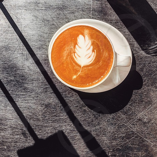 Coffee latte with leaf art on black table with long shadows in a white cup and saucer photo