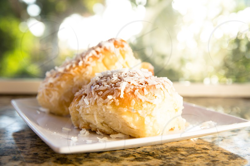 pastry on top of shredded cheese on white square plate photo