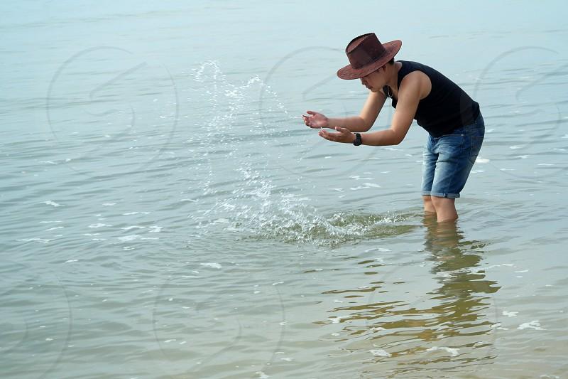man wearing black tank top splashing water on body of water photo