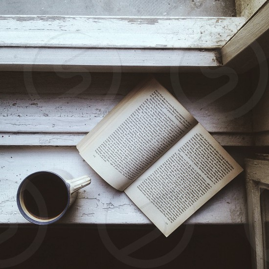 book and coffee next to window photo