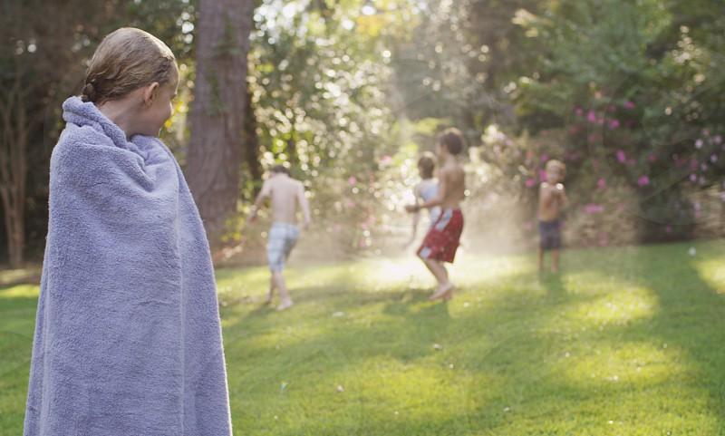 Kids playing sprinkler summer photo