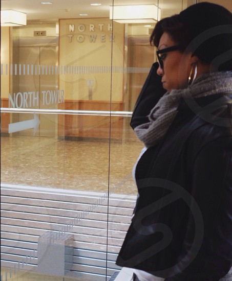 woman walking past north tower building in large hoops black sunglasses gray scarf and black jacket photo