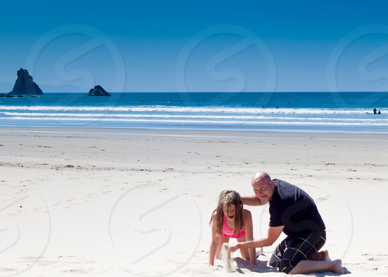 Father and Daughter Sand in the Face. Ocean Beach Waves Surfers photo