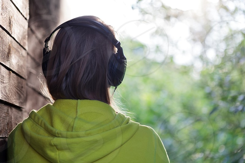 Back view of a girl in headphones listening to music outdoor. She standing by the wooden wall and enjoying nature scene photo
