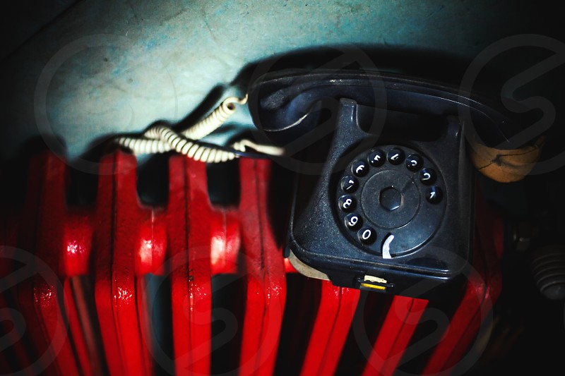 Old dusty and damaged telephone on red radiator.  photo