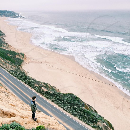 man standing on mountain top across seaside road photography photo