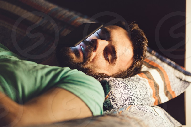 Young man using a smartphone in his bed at night photo