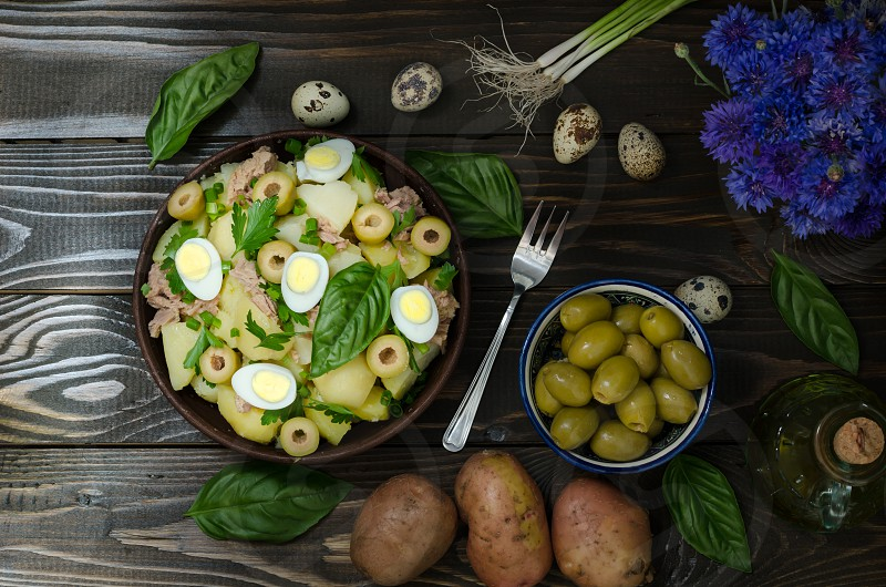 Potato salad on brown plate with ingredients on dark background photo