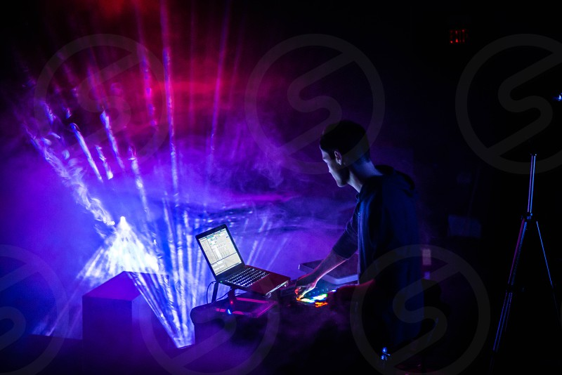 Disk Jockey with smoky background with disco lights photo