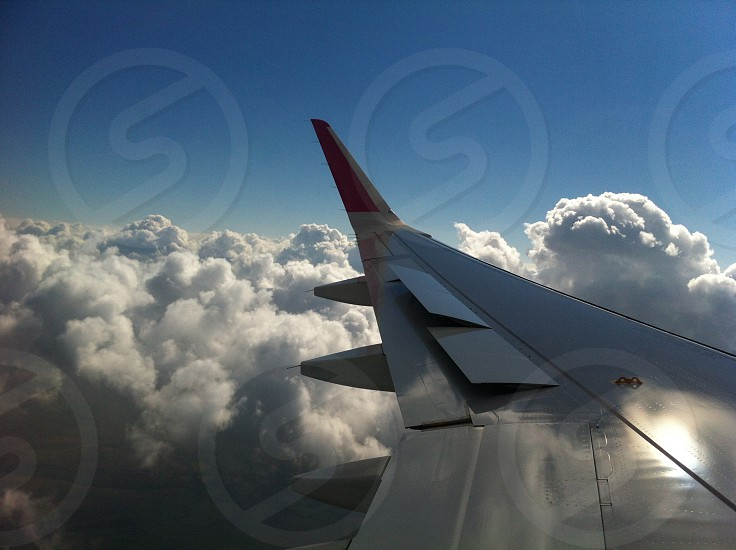 grey airplane wing over white clouds photo