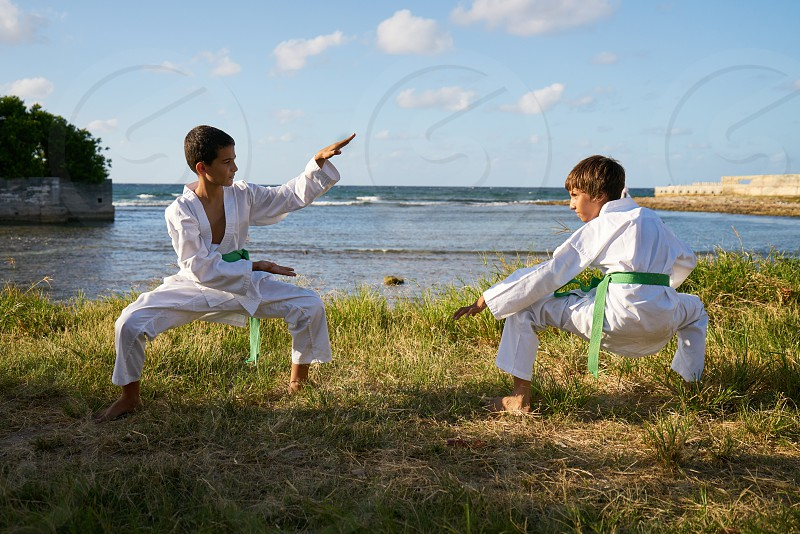 Children doing combat and extreme sports. Latino boys exercising in karate and traditional martial arts. Simulation of fight on the beach photo