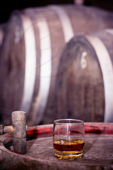 Glass of whiskey neat without ice on barrel in distillery with wooden barrels in the background photo
