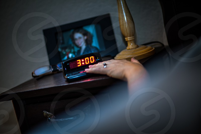 A woman's hand hits / turns off / slaps off a black plastic digital alarm clock on a nightstand with a photo / picture frame eye glasses and lamp.  Night 3:00 o'clock AM rings red numbers wood metal female girl lady fingers arm sleep wake early hair bed pillow blanket. photo