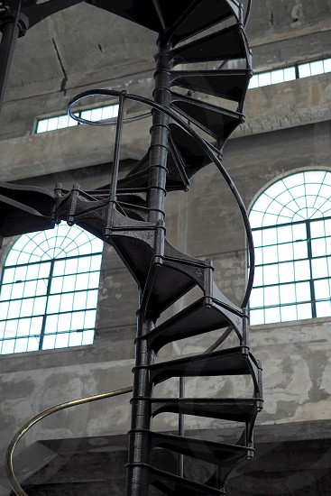 Spiral staircase and windows in industrial building. Iron. Stairs. Pattern. Frame. Framing. Old. Curves.  photo