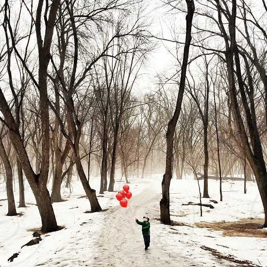 child in winter apparel in forest holding red balloons photo