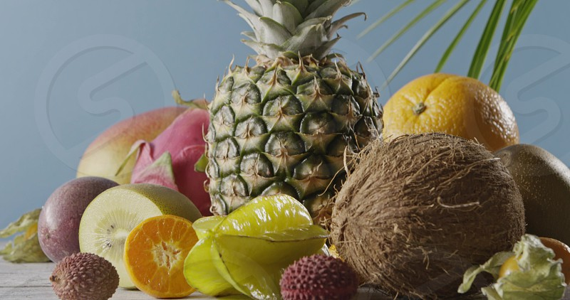 Ripe pineapple with fresh natural exotic fruits on a wooden table on a blue background. Vertical panoramic motion 4K UHD video 3840 2160p. Concept of vegetarian diet eating. photo