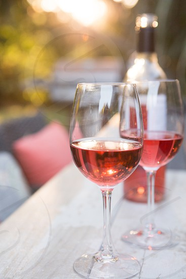 Rosé wine on wood table outdoor on a summer evening. photo