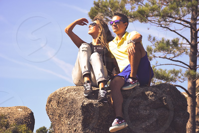 man and woman sitting on the rock photo