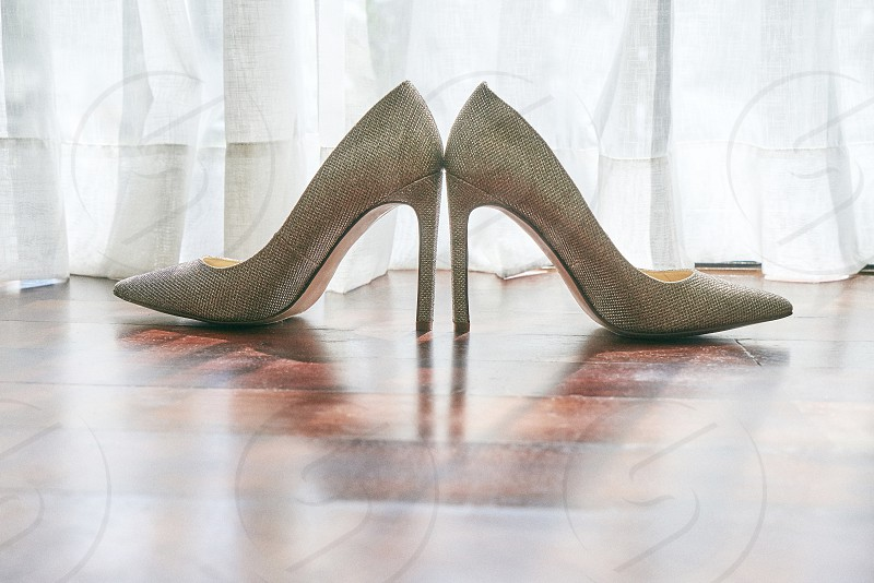 Women high heels shoes glitter and shiny texture on the wooden floor with light and shadow behind through curtain photo