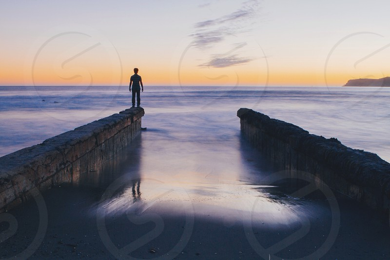man on cemented dock silhouette photo