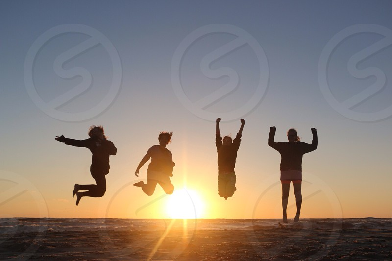 four persons jumping photo