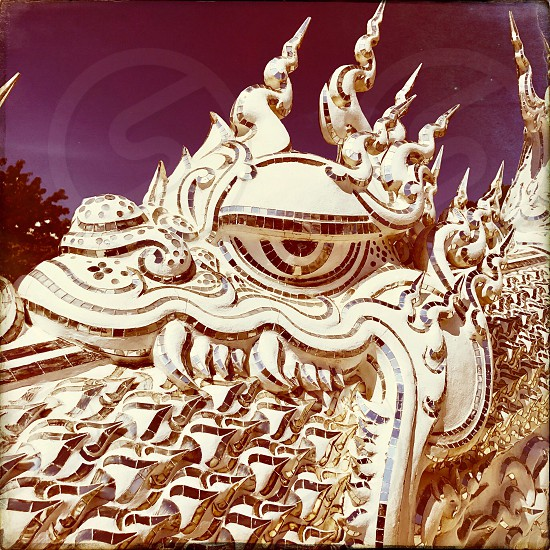 Outdoor day square filter colour Wat Rong Khun The White Temple Chiang Rai Thailand Thai Kingdom of Thailand travel tourism tourist wanderlust summer summertime temple Buddhist Buddhism spiritual pure holy dragon monster carved ornate elaborate art modern sculpture sculpted east eastern hands silver mirror mosaic magical mythical blue sky dragon eye shine photo