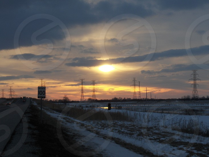 sunset speed limit sign high tension towers snow photo