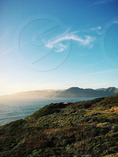 green hill near sea photo