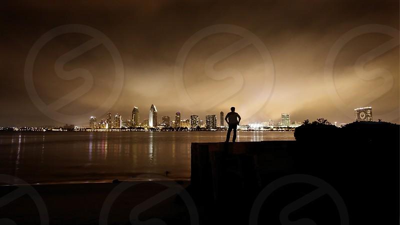 lone man standing alone night city water beach island san diego california photo