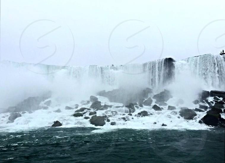 waterfalls on black rocky body of water under gray skies photo