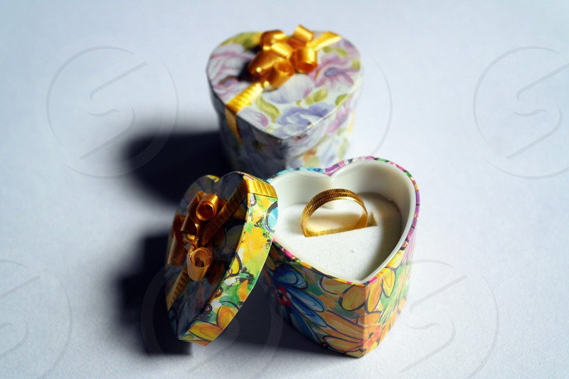gold ring on yellow blue and green floral heart-shaped box photo