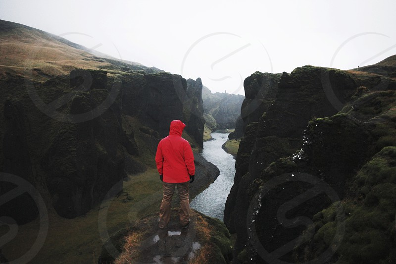 person wearing red hoodie standing on cliff facing river between brown mountains photo