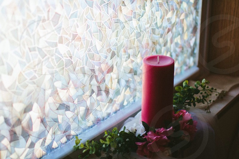red candle beside a window photography photo