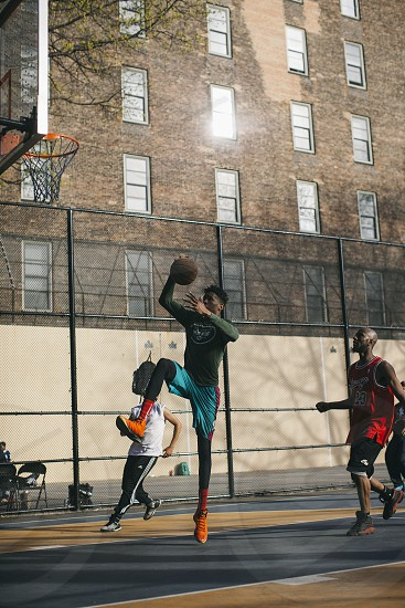 man wearing green long sleeve sweatshirt and teal jersey shorts with orange shoes dunking basketball during daytime photo