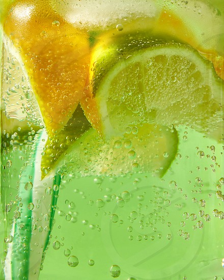 A natural fruit background with macro lime slices lemon and a colored drinking plastic straw in a glass jar with aerated gassed bubbles. Concept of cold alcoholic or non-alcoholic summer drinks. photo