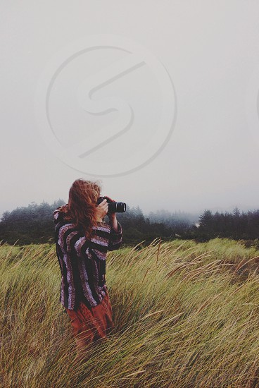 woman in striped shirt taking picture in field photo